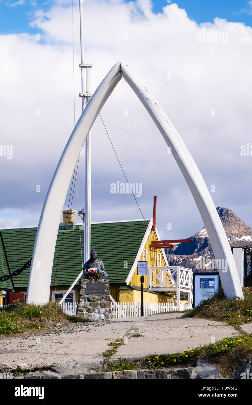 View to Jorgen C F Olsen monument statue outside first and oldest house through Whale bones arch in museum. Sisimiut - Stock Image