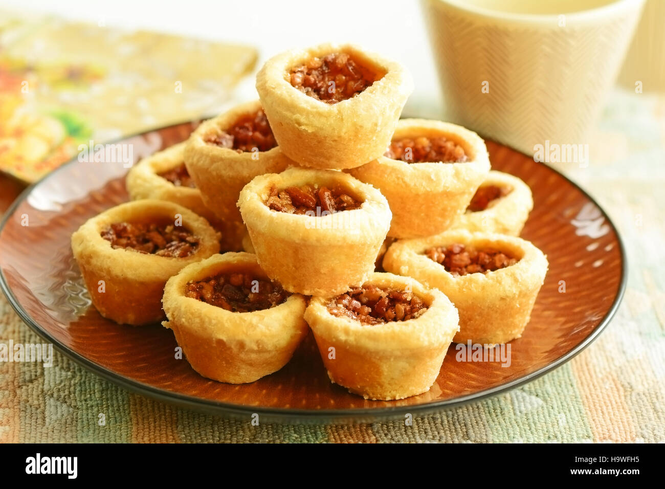 Delicious little pecan tarts with flaky pastry and coffee in horizontal format - Stock Image