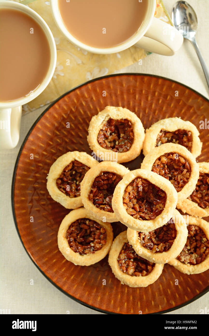 Delicious little pecan tarts with flaky pastry and coffee with cream in vertical format from overhead - Stock Image
