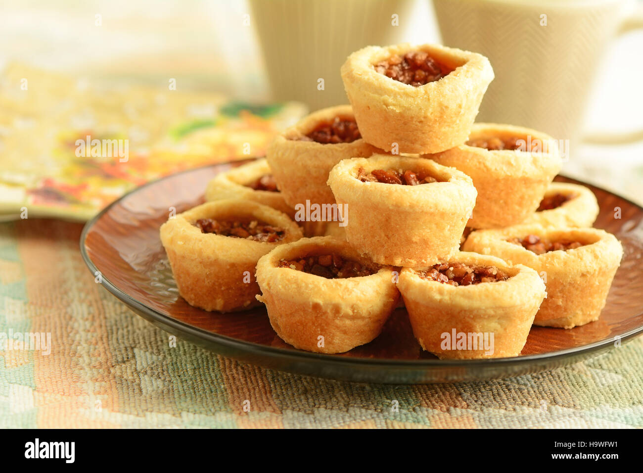 Delicious little pecan tarts with flaky pastry and coffee in vertical format - Stock Image