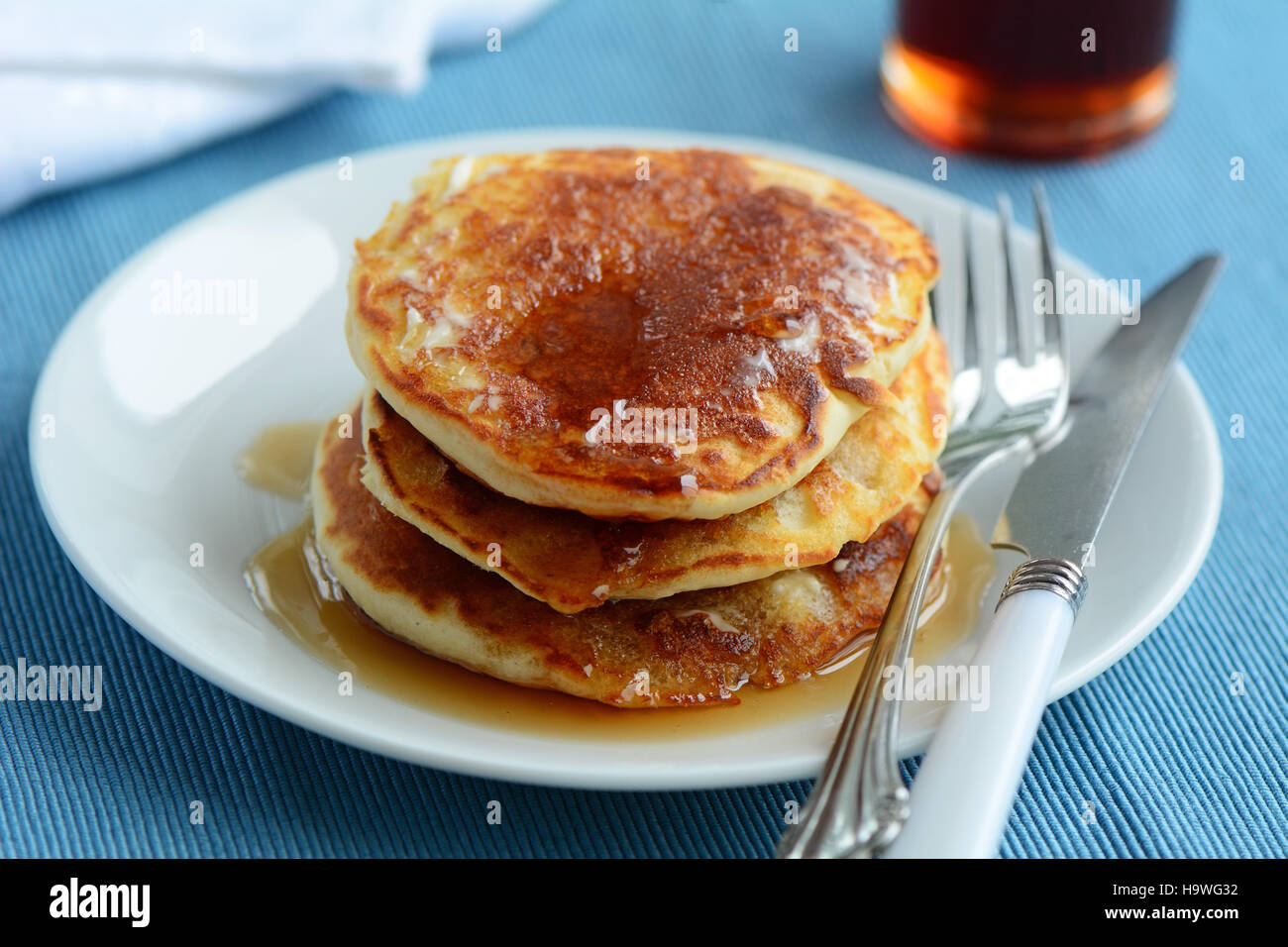 Fresh home made buttermilk pancakes with maple syrup shot in natural light - Stock Image