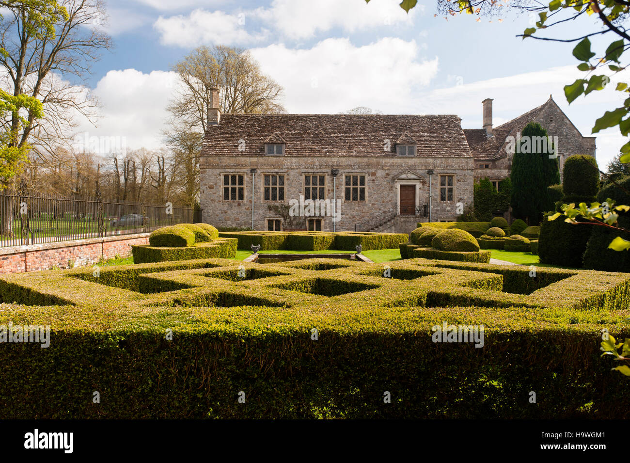 View over hedging towards the west front at Avebury Manor, Wiltshire. - Stock Image