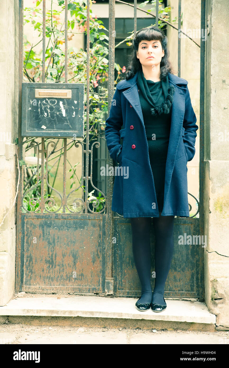 A retro girl standing in front of an old house. Stock Photo