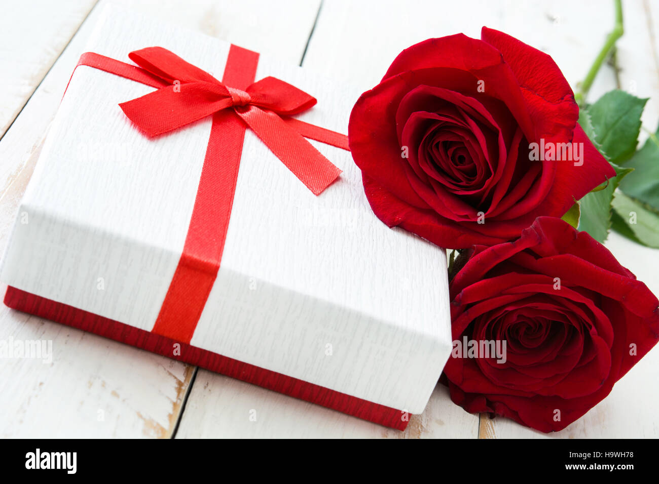 White gift box and roses on white wooden table.closeup Stock Photo