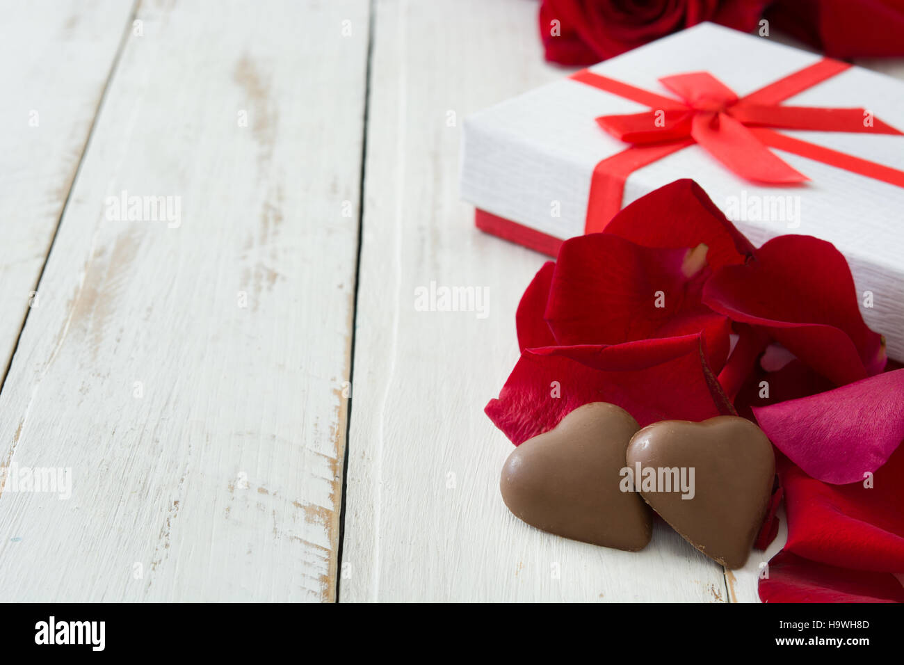 White gift box, roses and chocolate with heart shape on wooden table.copyspace Stock Photo