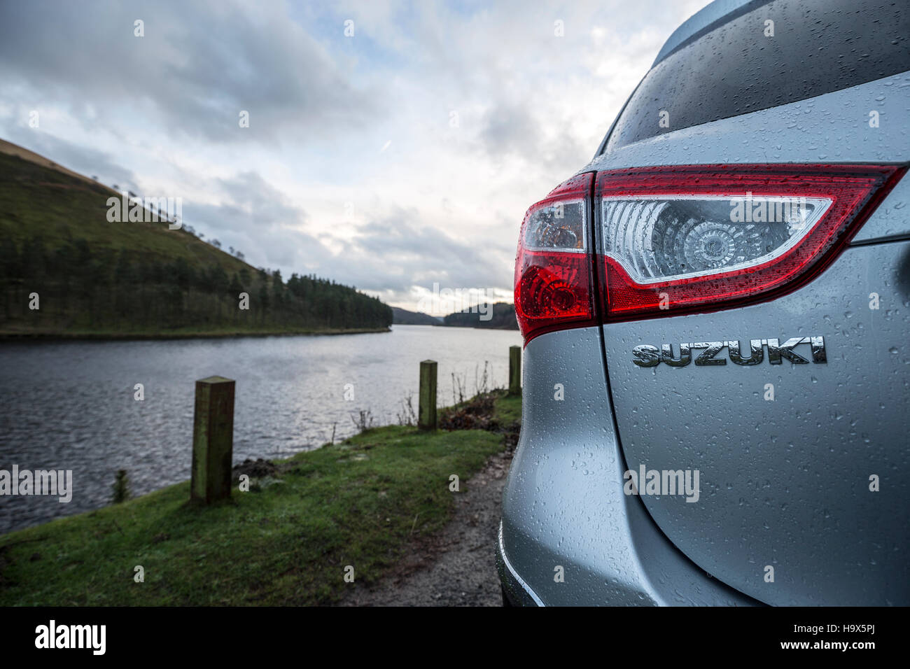 Back light of rain covered Suzuki car with water in the background Derbyshire England - Stock Image