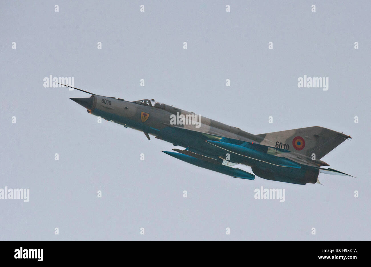 A Romanian Air Force Mikoyan-Gurevich MiG-21 supersonic jet fighter aircraft flies over a missile site during a - Stock Image