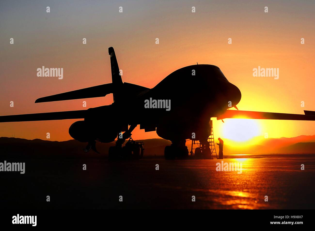 A B-1B Lancer jet-powered heavy strategic bomber aircraft sits on the runway at sunset at the Ellsworth Air Force - Stock Image