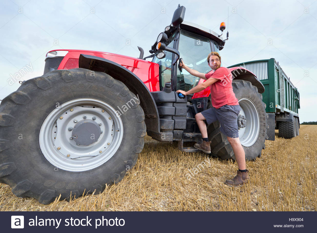 Farmer Climbing Into Cab Of Tractor At Harvest Time - Stock Image