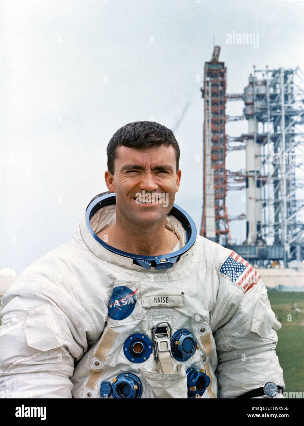 NASA Apollo 13 lunar landing mission astronaut Fred Haise poses dressed in a spacesuit in front of the Saturn V - Stock Image