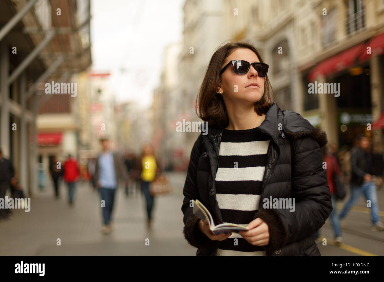 Young woman is on the street and looking for a place to visit ,they are using a travel guide to explore where they - Stock Image