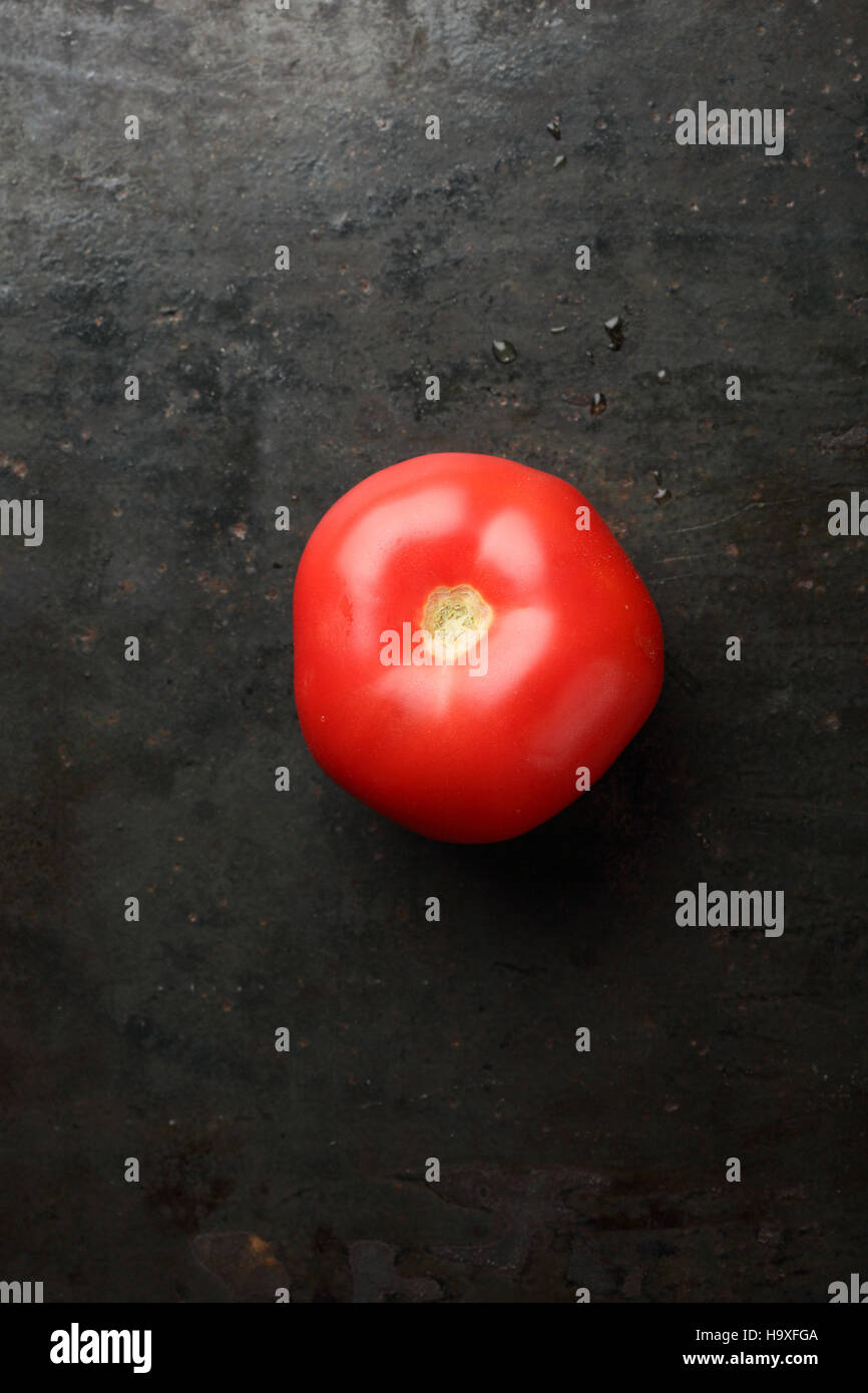One ripe tomato on dark background, food top view - Stock Image
