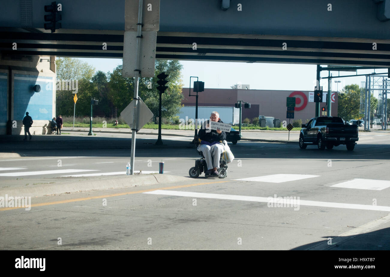 Handicapped man in wheelchair holding sign saying he is suffering from 'traumatic brain injury'. Minneapolis - Stock Image