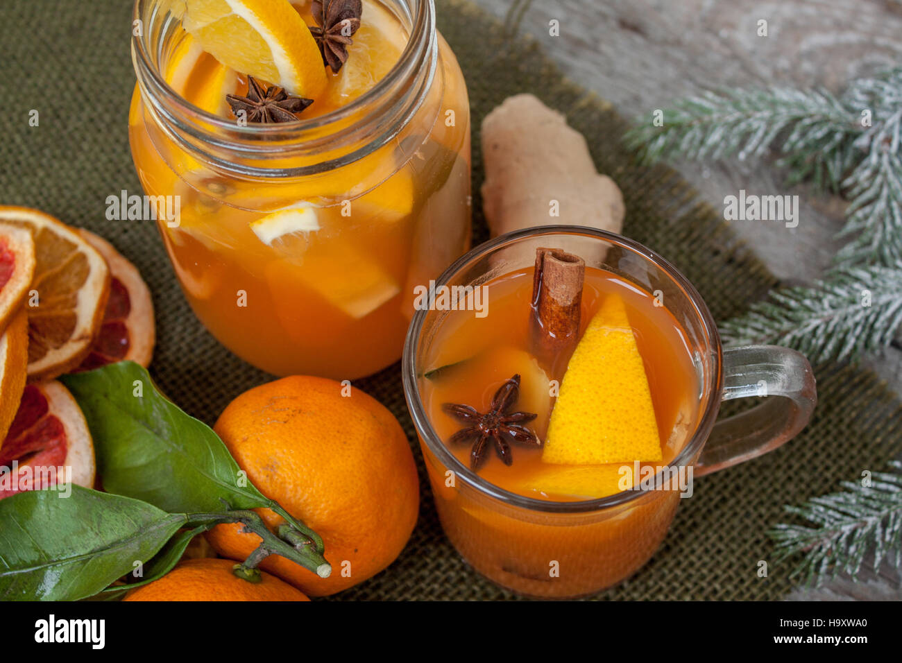 Winter healing ginger drink with lemon, honey and oranges. Cinnamon, star anise, fir twigs, tangerines, dried grapefruit. - Stock Image