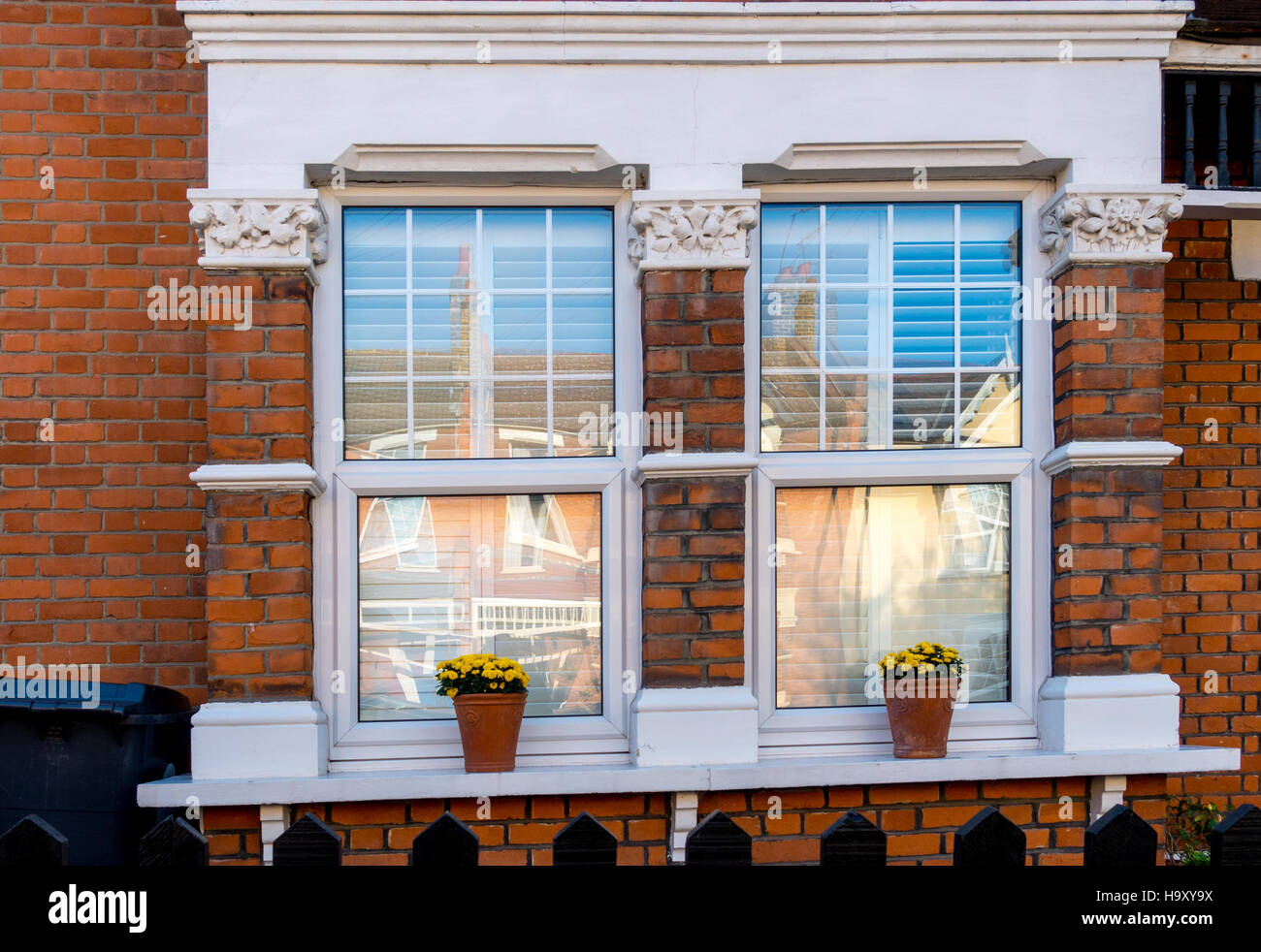 A typical London Edwardian era house with plats on the window cill - Stock Image