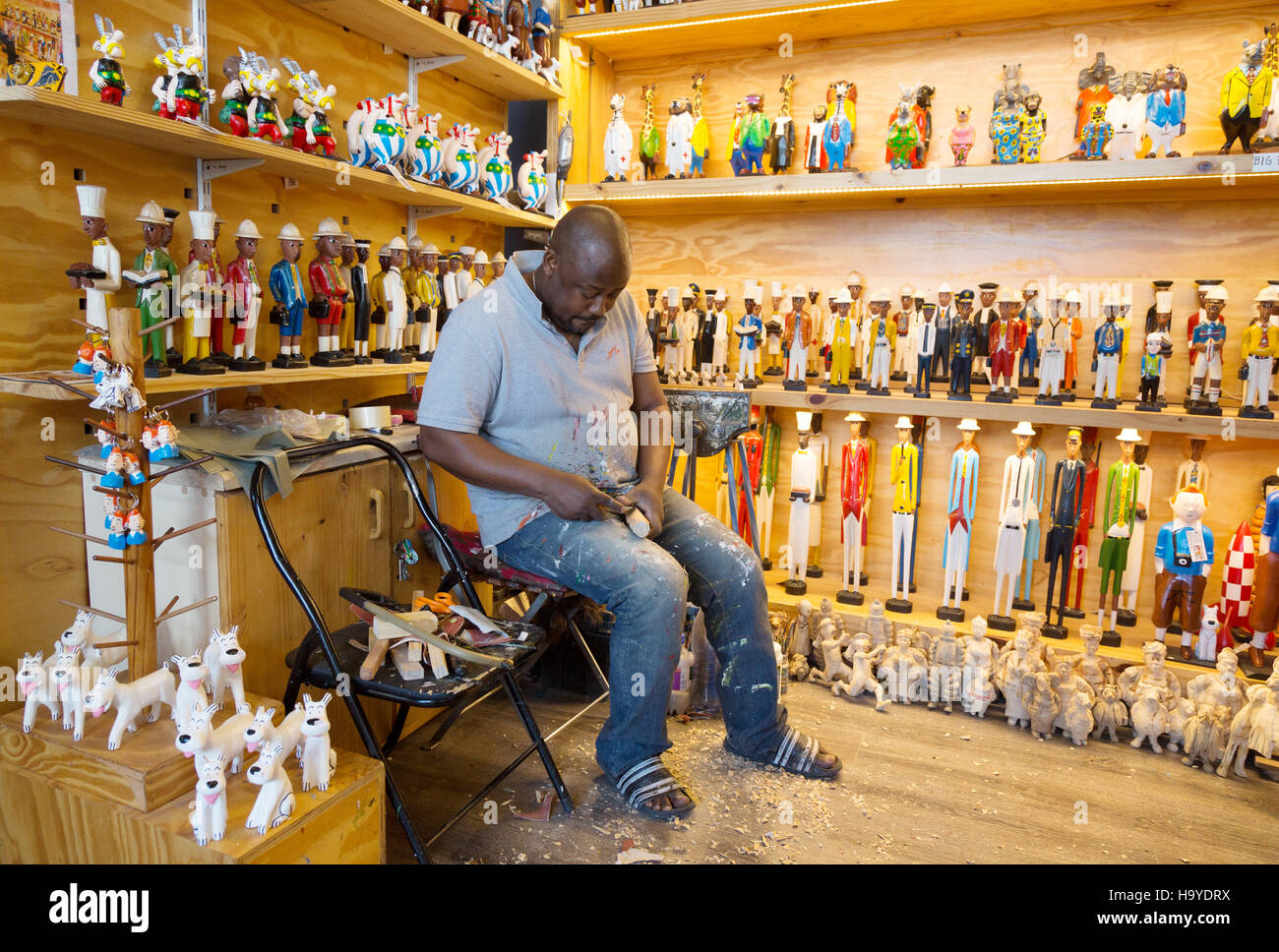 A craftsman at work carving wooden toys in a craft shop 13931e0d870e