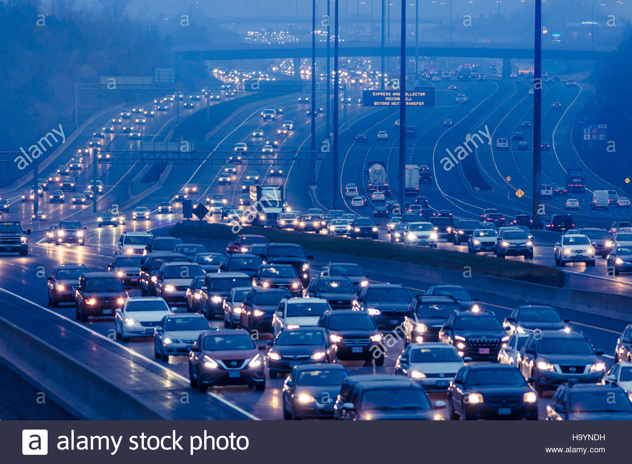 traffic morning rush hour heavy congestion commuting into Toronto rain about 7:45 AM on the 14 lane Highway 401 - Stock Image
