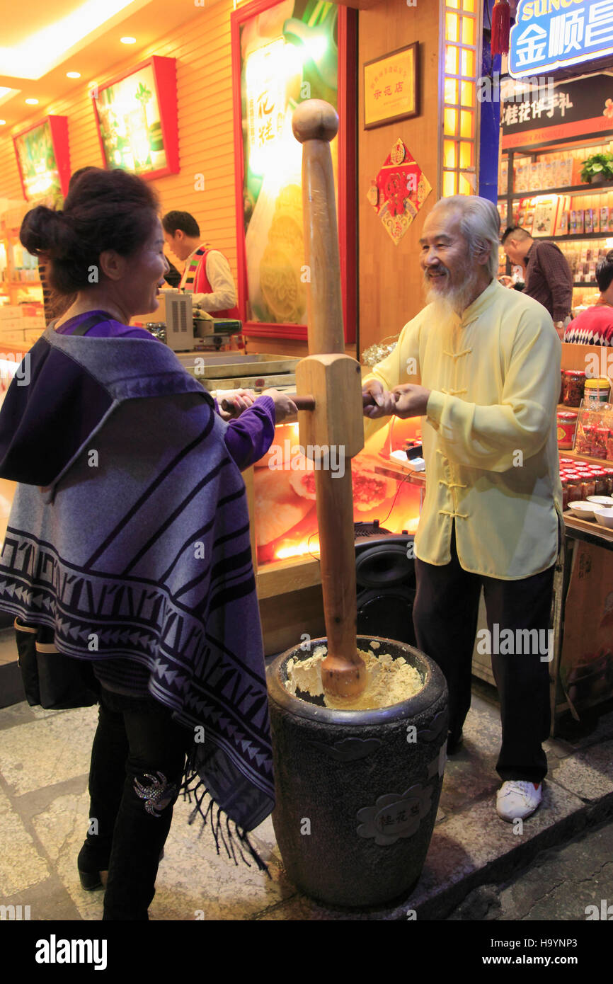 China, Guangxi, Yangshuo, pastry shop, beating paste, people, - Stock Image