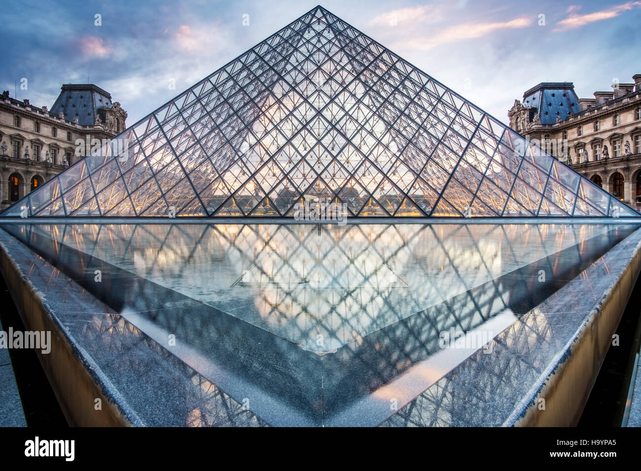 The glass pyramid entrance to the Louvre, designed by architect I.M.Pei. Evening shot in summer. - Stock Image