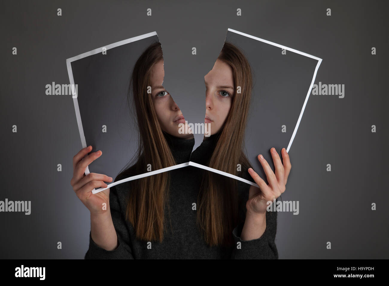 Surreal image - Girl holds up a torn photo of herself, with invisible head. - Stock Image