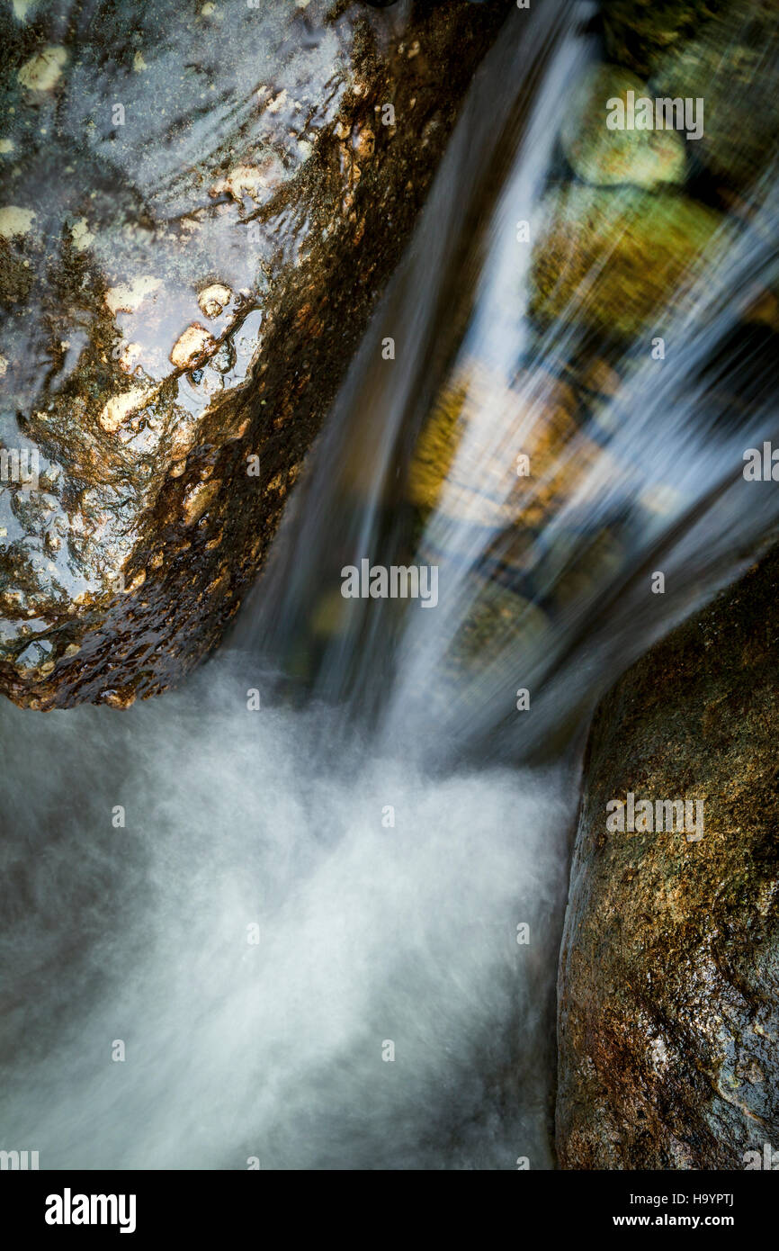 A Small waterfall between stepping stones in the duddon valley, Lake Distraict, Cumbria - Stock Image