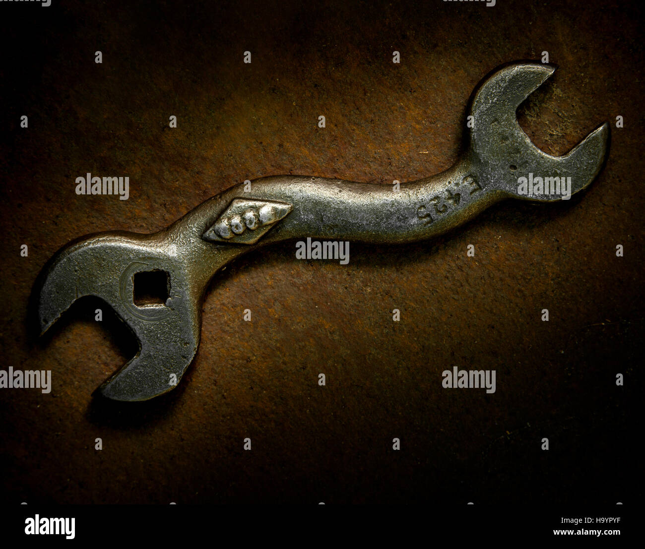 Photograph using Light Painting of an old bent spanner on a rusty metal background. - Stock Image