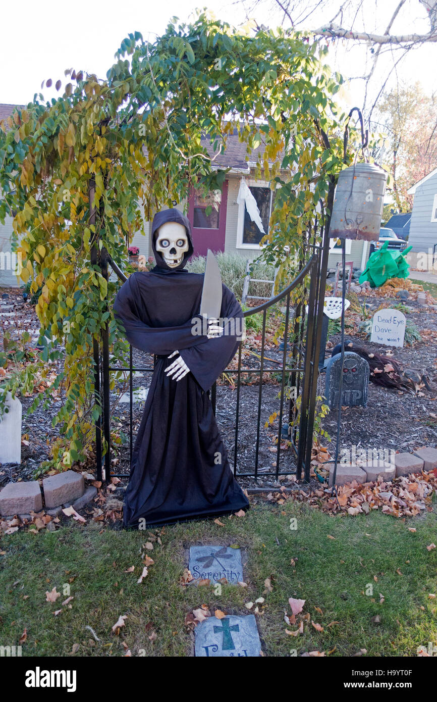 Halloween grim reaper skeleton with large cleaver guarding cemetery gate in front yard of house. Fergus Falls Minnesota - Stock Image