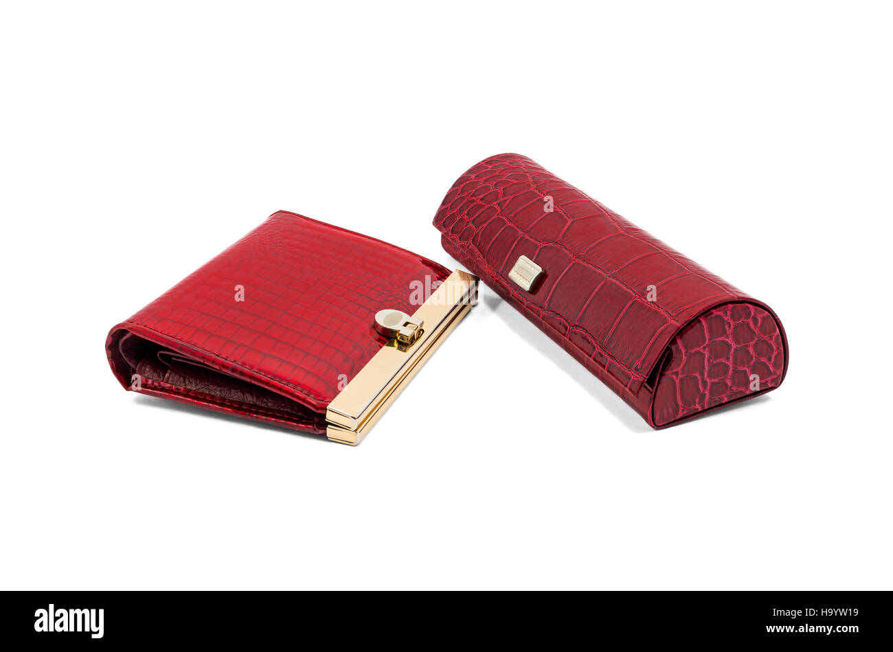 Red wallet and glasses case made of crocodile leather on a white background - Stock Image