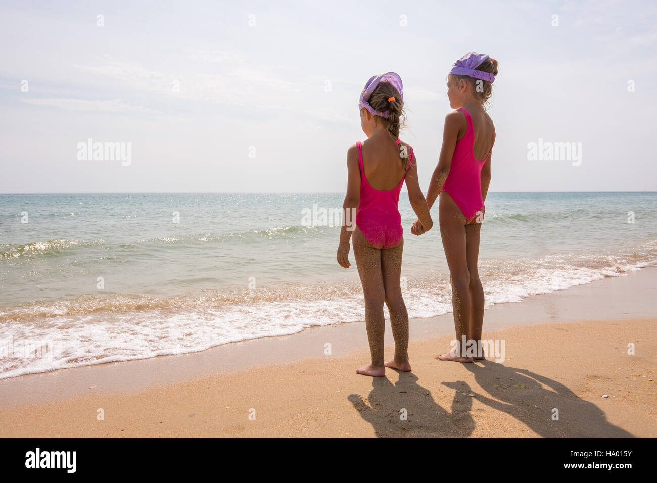 Two girls in bathing suits standing on the beach and look at the horizon Stock Photo