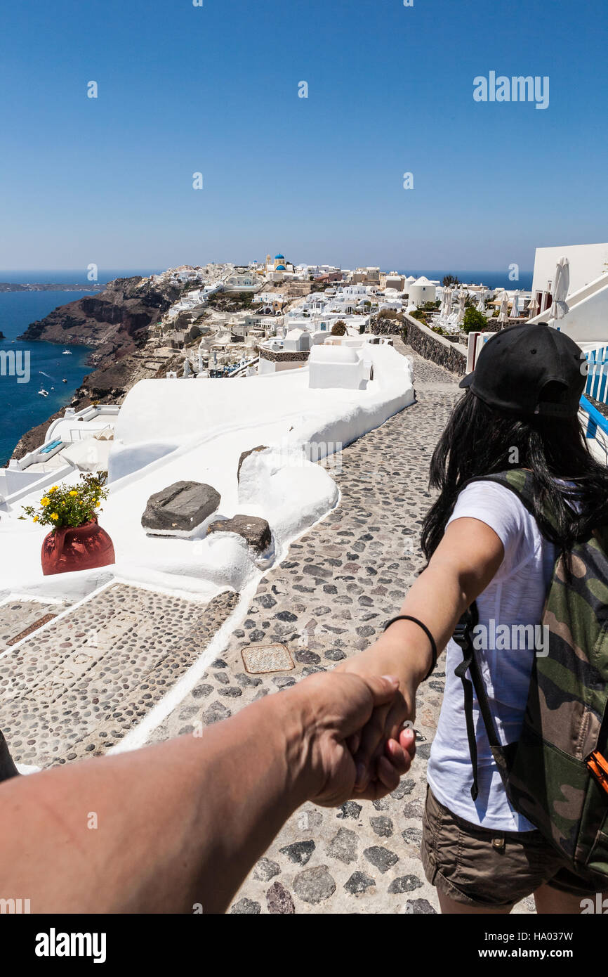 Young girl leading her friend down a path to Oia, Santorini, Greece - Stock Image