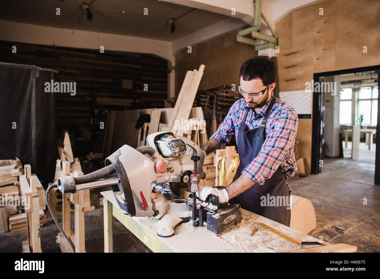 Young craftsman in uniform working at carpentry - Stock Image