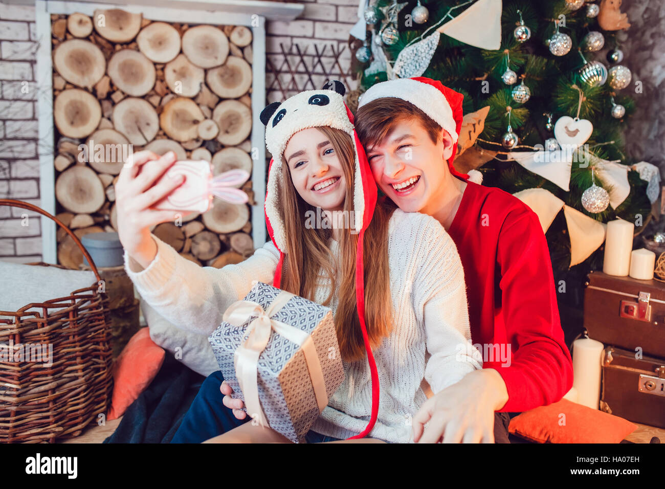 Young Couple In Love Sitting Near Christmas Tree Funny Hats Having Fun And Make Selfie New Year