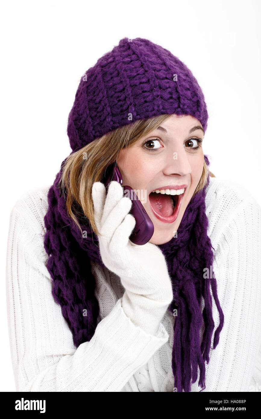 3377cb24b60d Young woman wearing a purple woolen cap and scarf talking on a mobile  telephone