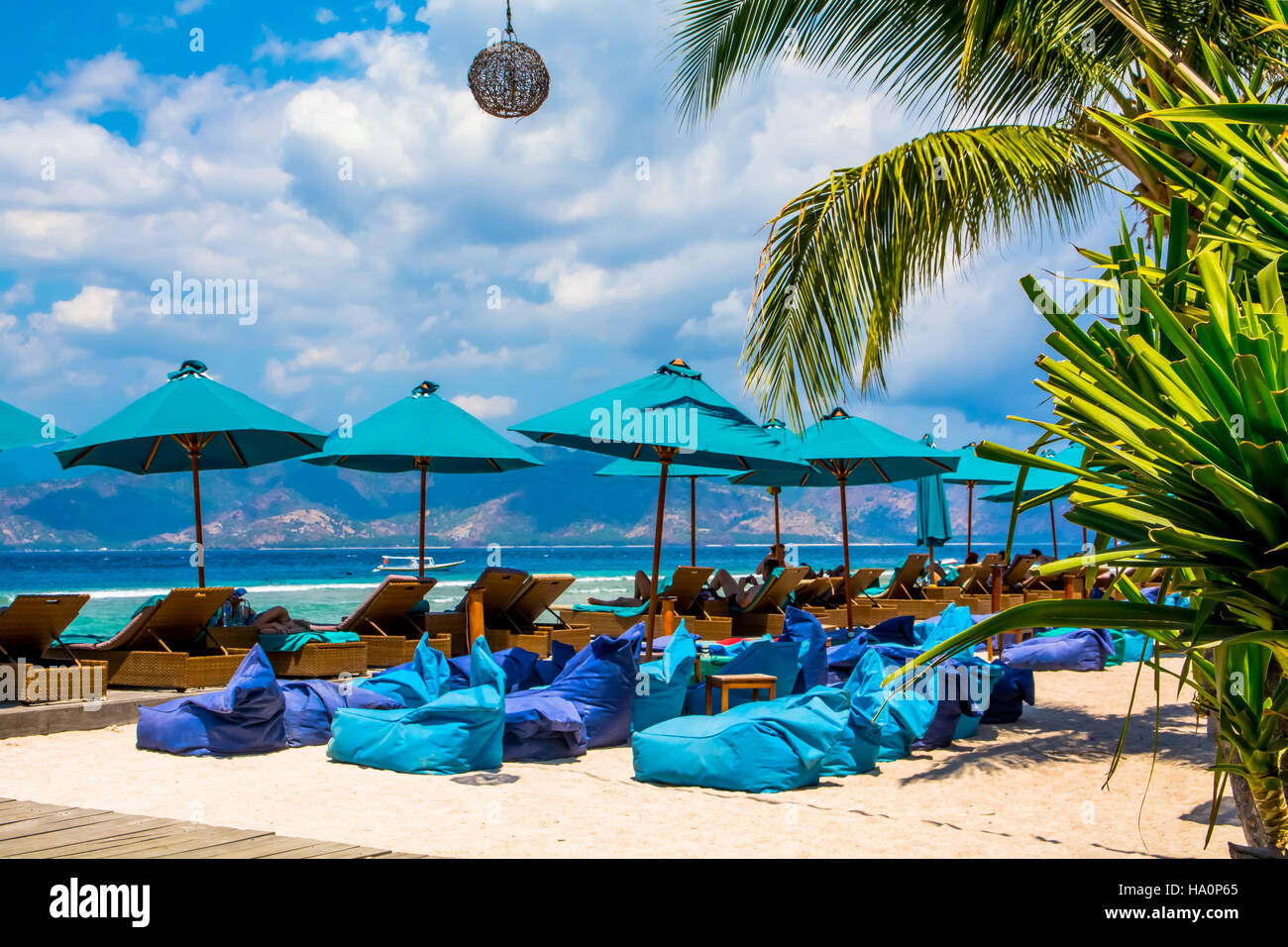 Beach  Lounge Chairs And Bean Bags On Sand Against Blue Sky and Sea - Stock Image