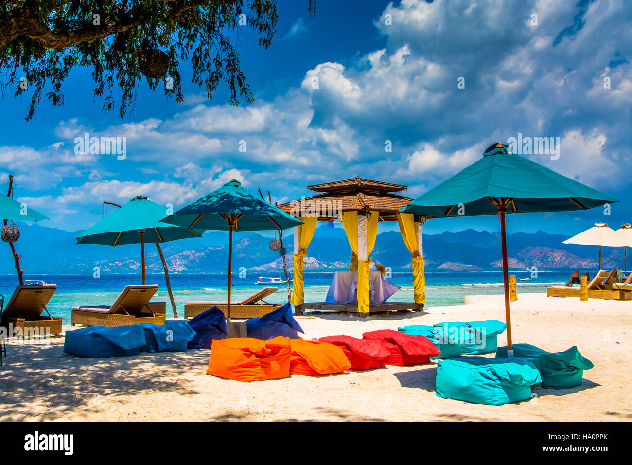 Parasols By Lounge Chairs And Bean Bags On Sand At Beach Against Sky - Stock Image