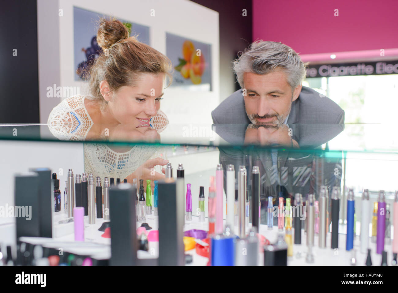 Man and lady gazing into counter of vaporisers - Stock Image