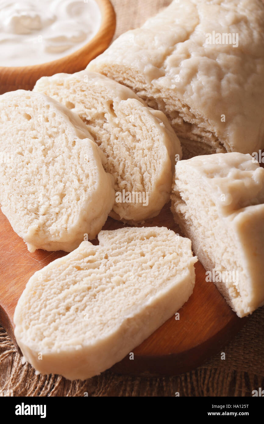Traditional sliced yeast knodel close-up on the table. vertical - Stock Image