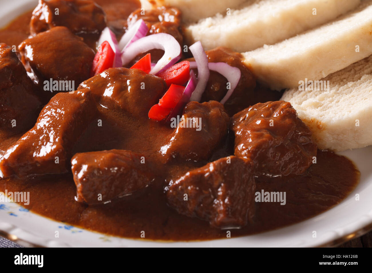 Czech cuisine: beef goulash with Knodel macro on a plate. Horizontal Stock Photo