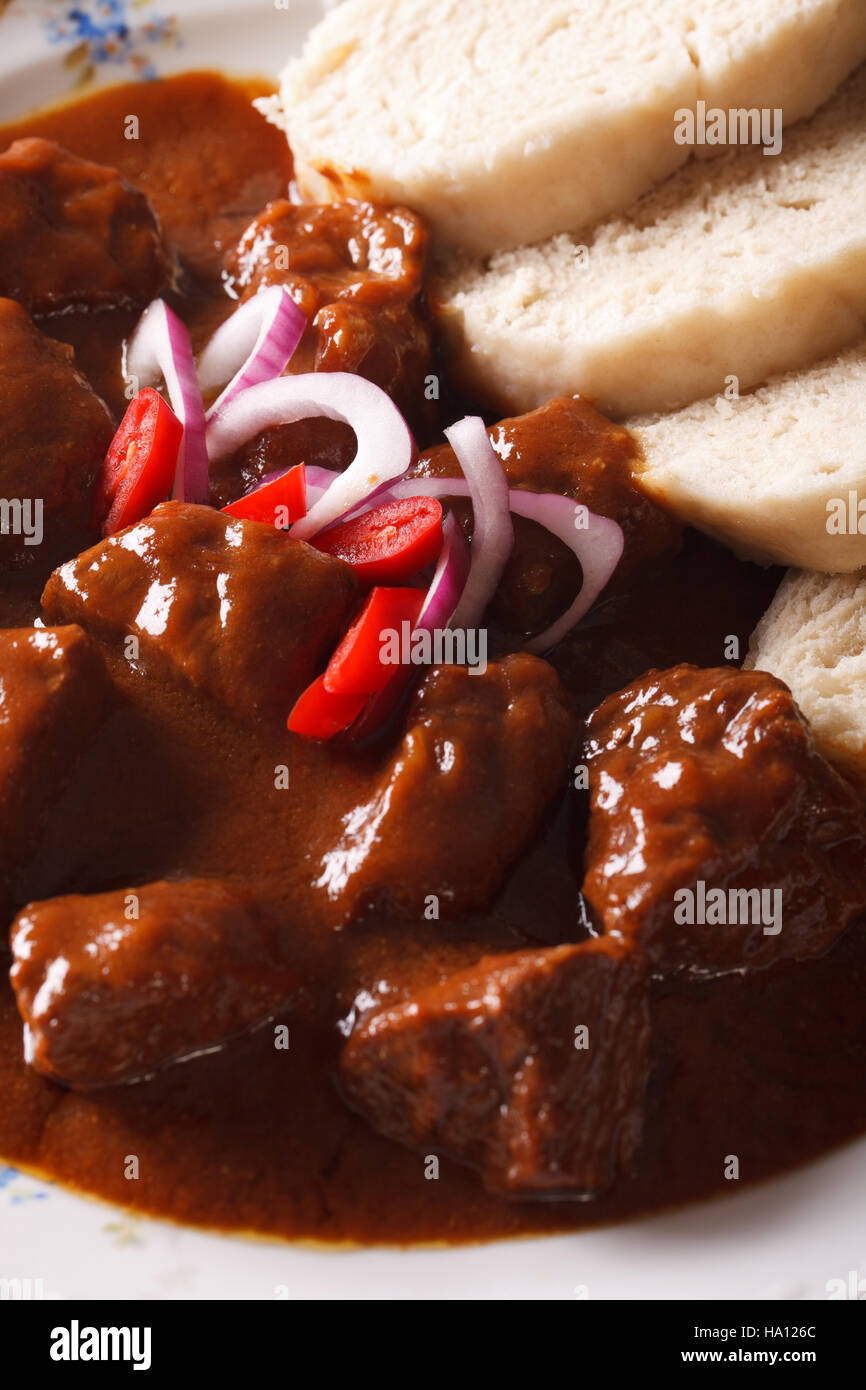 Czech cuisine: beef goulash with Knodel macro on a plate. vertical - Stock Image
