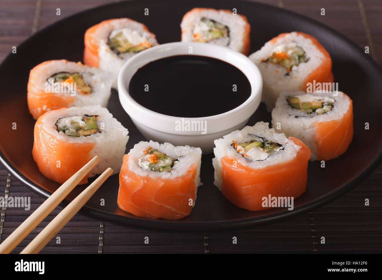 Sushi roll philadelphia and soy sauce , closeup on a plate. Horizontal - Stock Image
