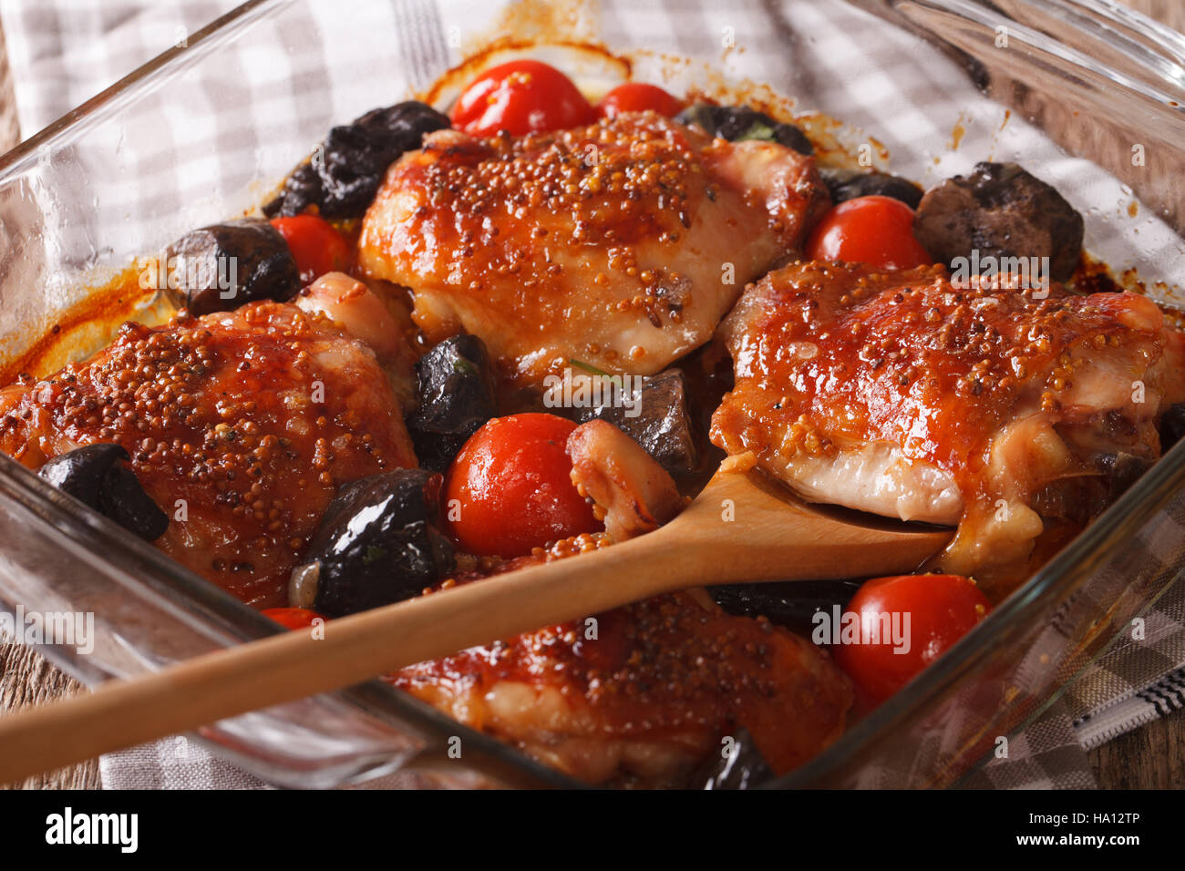chicken thigh baked with tomatoes and porcini mushrooms close up in baking dish on the table. Horizontal - Stock Image