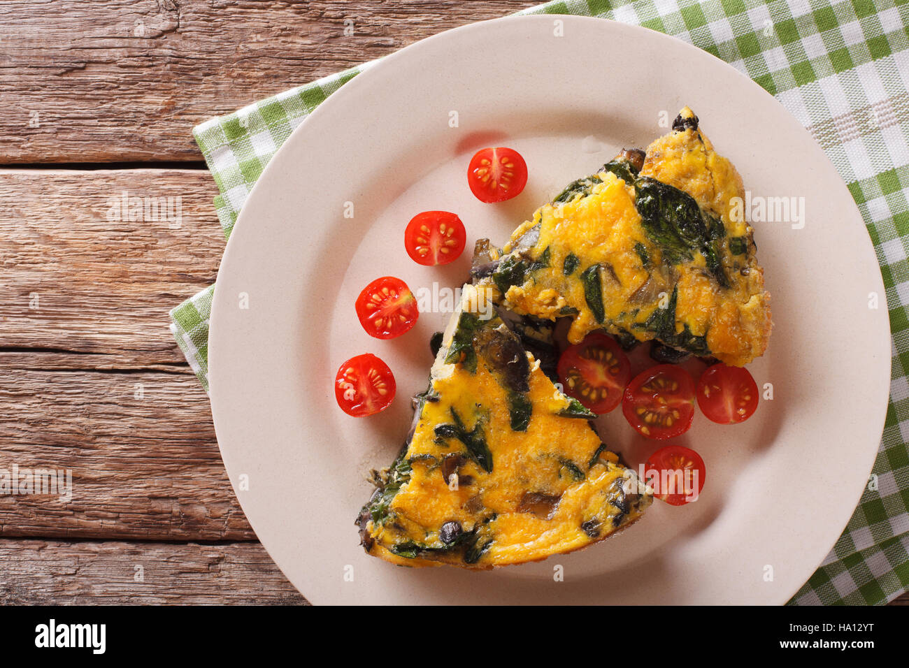 sliced frittata with spinach, cheddar cheese and mushrooms on a plate on a table close-up. Horizontal view from - Stock Image