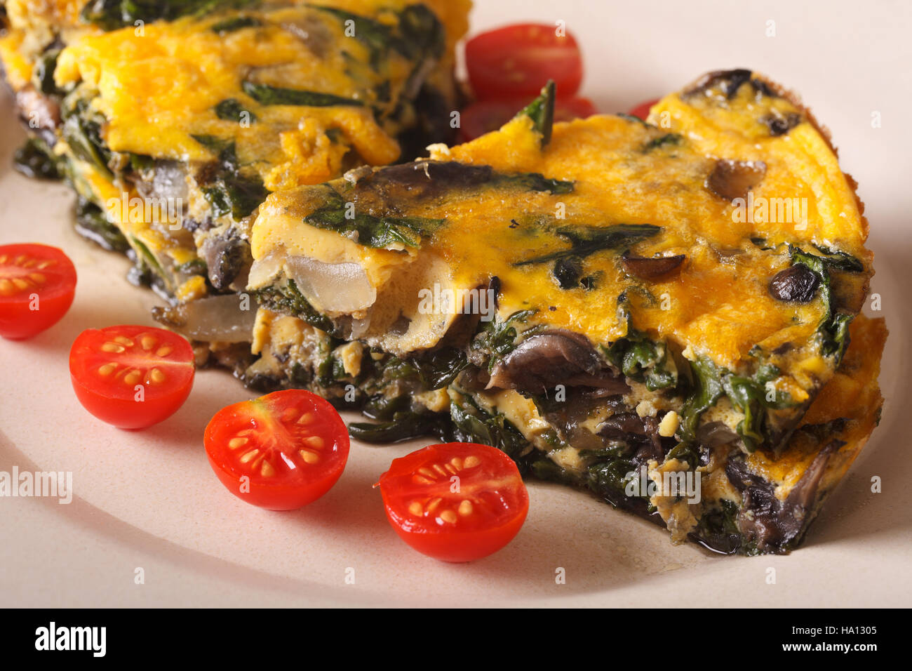 Frittata with spinach and mushrooms on a plate close-up. horizontal - Stock Image