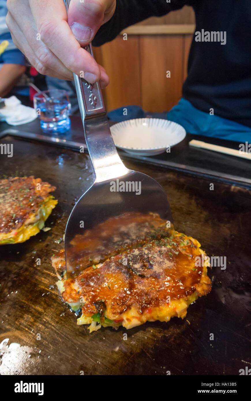 cutting Okonomiyaki, typical japanese dish, Japan - Stock Image