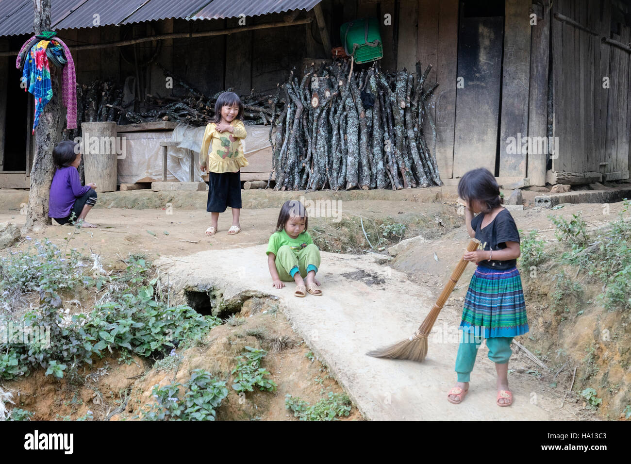 ethnic Vietnamese children playing and sweeping in the tribal village Lao Chai in Sapa, Vietnam, Asia - Stock Image