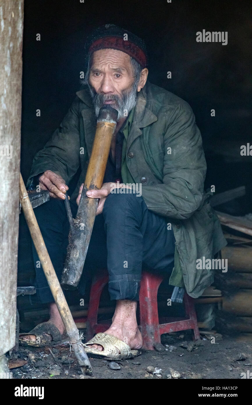 ethnic Vietnamese old man smoking his pipe in Ta Phin, Lao Cai in Sapa, Vietnam, Asia - Stock Image