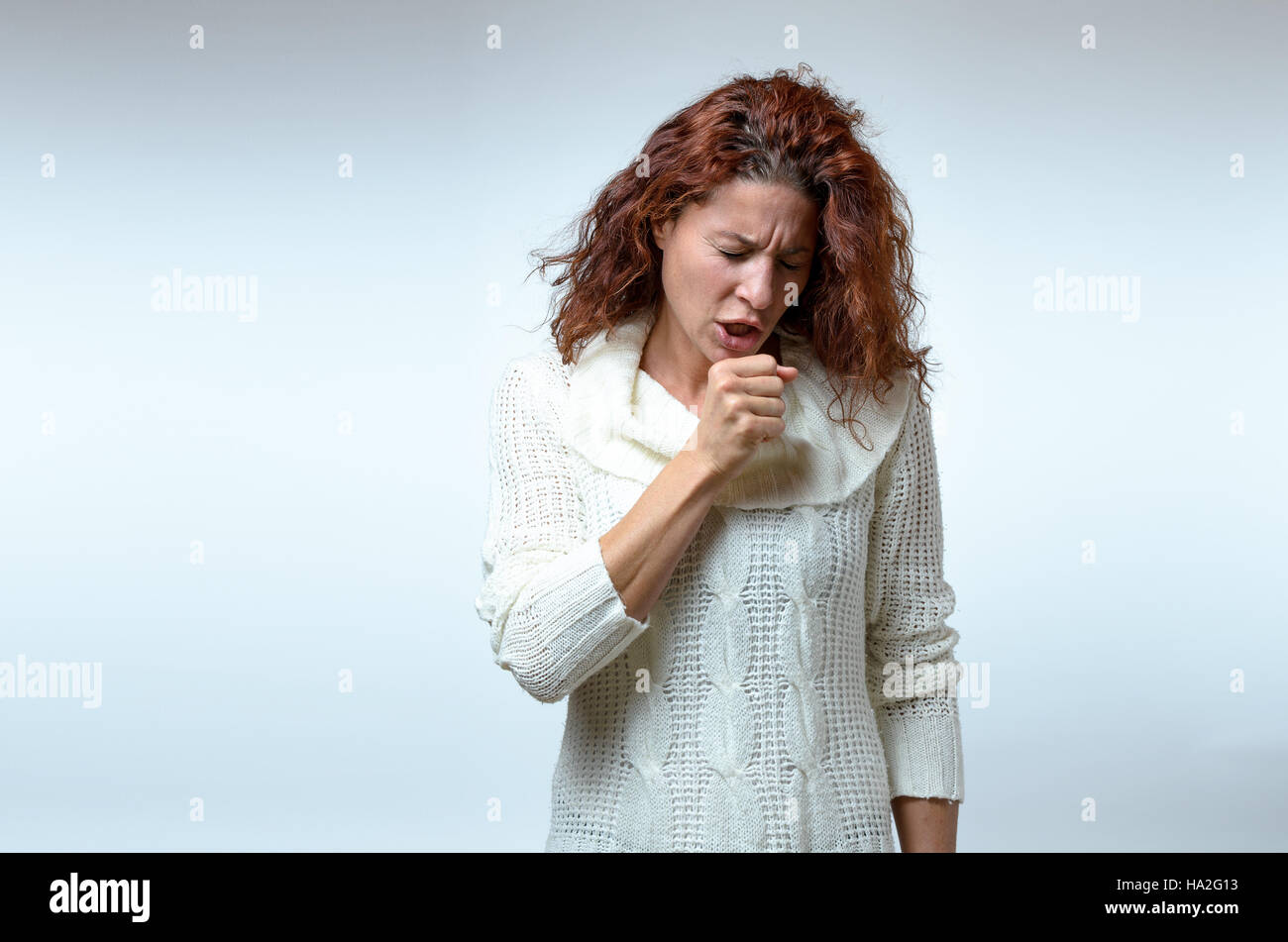 Attractive young woman in stylish winter fashion standing coughing raising her fist to her mouth in a healthcare - Stock Image