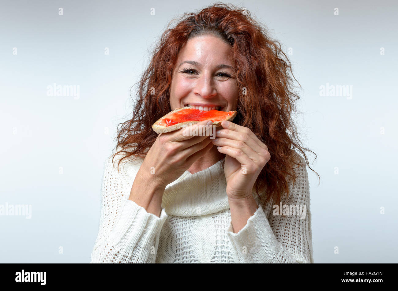 Smiling happy woman biting into colorful red berry jam on a slice of bread as she grins at the camera, close up - Stock Image