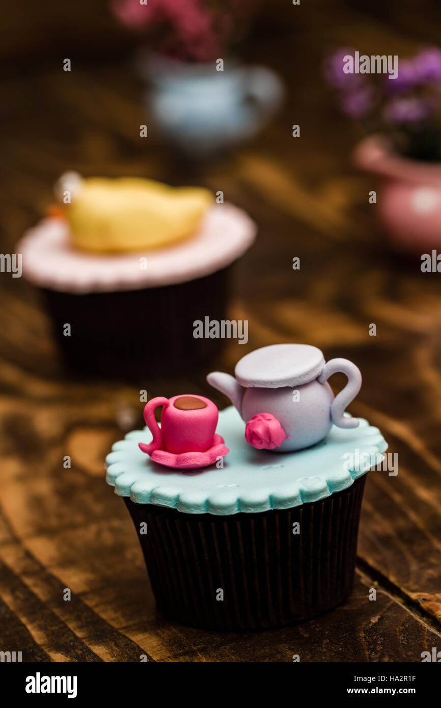 Colorful cupcakes with cute figures on wooden background - Stock Image