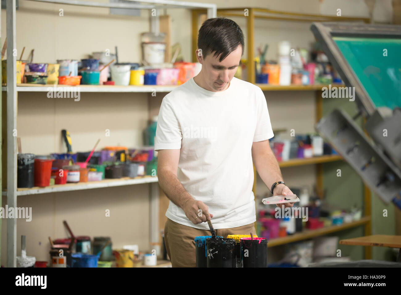 Young man combining CMYK - Stock Image